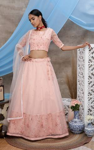Look Pretty In Light Peach Colored Designer Lehenga Choli. This Pretty Piece Is Net Based Beautified With Elegant Tone To Tone Embroidery.