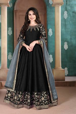 Here Is A Designer Floor Length Suit In Black Color Paired With Grey Colored Dupatta. Its Pretty Embroidered Top Is Fabricated on Slub Silk Paired With Santoon Bottom and Net Fabricated Dupatta. Buy Now.