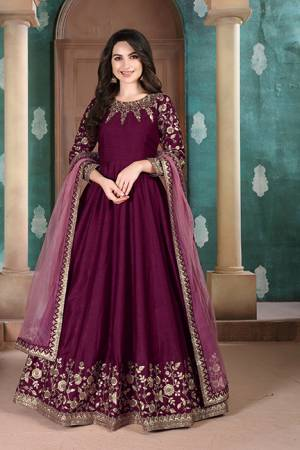 Here Is A Designer Floor Length Suit In Wine Color Paired With Grey Colored Dupatta. Its Pretty Embroidered Top Is Fabricated on Slub Silk Paired With Santoon Bottom and Net Fabricated Dupatta. Buy Now.