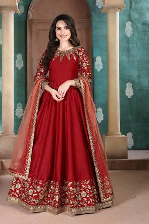 Here Is A Designer Floor Length Suit In Red Color Paired With Grey Colored Dupatta. Its Pretty Embroidered Top Is Fabricated on Slub Silk Paired With Santoon Bottom and Net Fabricated Dupatta. Buy Now.