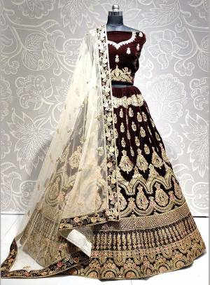 Get Ready For The Upcoming Wedding Season With This Heavy Designer Lehenga Choli In Brown Color Paired With Off-White Colored dupatta. This Lehenga Choli Is Fabricated On Velvet Paired With Net Fabricated Dupatta.