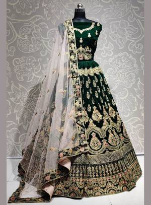 Get Ready For The Upcoming Wedding Season With This Heavy Designer Lehenga Choli In Dark Green Color Paired With Off-White Colored dupatta. This Lehenga Choli Is Fabricated On Velvet Paired With Net Fabricated Dupatta.