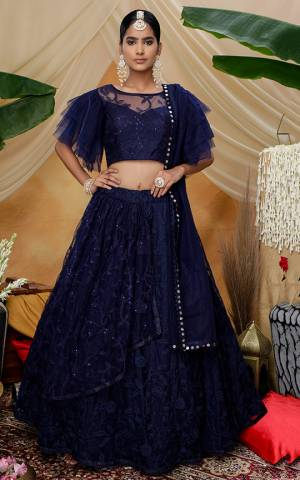 Here Is A Very Pretty Designer Lehenga Choli For The Upcoming Wedding Season In All Over Navy Blue Color. This Trendy Lehenga Choli Is Fabricated On Net Beautified With Heavy Yet Subtle Tone To Tone Embroidery. Buy This Lovely Piece Now.