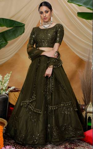 Here Is A Very Pretty Designer Lehenga Choli For The Upcoming Wedding Season In All Over Olive Green Color. This Trendy Lehenga Choli Is Fabricated On Net Beautified With Heavy Yet Subtle Tone To Tone Embroidery. Buy This Lovely Piece Now.