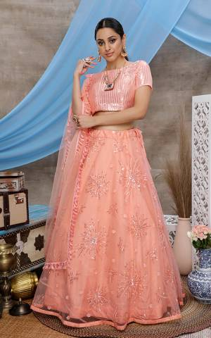 Here Is A Very Pretty Designer Lehenga Choli For The Upcoming Wedding Season In All Over Peach Color. This Trendy Lehenga Choli Is Fabricated On Net Beautified With Heavy Yet Subtle Tone To Tone Embroidery. Buy This Lovely Piece Now.
