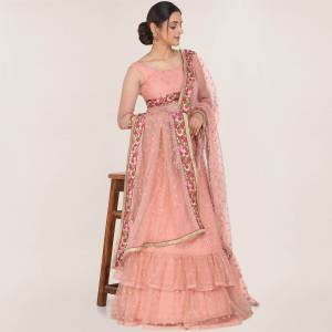 Here Is A Trendy Heavy Designer Lehenga Choli In Peach Color. This Beautiful Patterned Lehenga Choli And Dupatta Are Fabricated On Net and Has Quite Heavy Embroidery Over It. Buy Now.