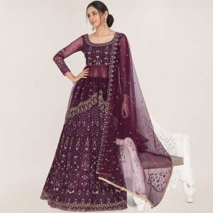 Here Is A Trendy Heavy Designer Lehenga Choli In Wine Color. This Beautiful Patterned Lehenga Choli And Dupatta Are Fabricated On Net and Has Quite Heavy Embroidery Over It. Buy Now.