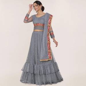 Here Is A Trendy Heavy Designer Lehenga Choli In Grey Color. This Beautiful Patterned Lehenga Choli And Dupatta Are Fabricated On Net and Has Quite Heavy Embroidery Over It. Buy Now.