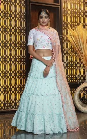 Look Pretty In This Subtle Color Pallete Lehenga Choli In White Colored Blouse Paired With Sky Blue Colored Lehenga And Peach Colored Dupatta. Its Blouse And Lehenga Are Cotton Based Paired With Net Fabricated Dupatta.