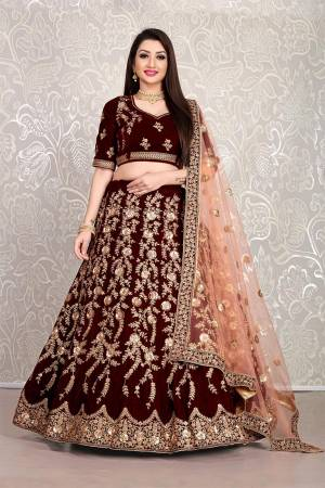 Here Is An Attractive Looking Heavy Designer Lehenga Choli In Maroon Color Paired With Peach Colored Dupatta. This Lehenga Choli Is Velvet Based Paired With Net Fabricated Dupatta. Buy Now.