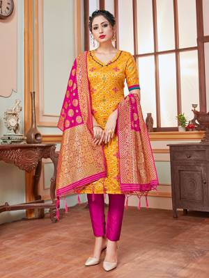 Celebrate This Festive Season In A Proper Traditional Look Wearing This Weaved Straight Suit In Musturd Yellow Colored Top Paired With Contrasting Dark Pink Colored Bottom And Dupatta. This Pretty Suit Is Banarasi Silk Based Beautified With Weave. Its Fabric Gives A Rich Look To Your Personality.