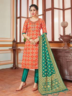 Celebrate This Festive Season In A Proper Traditional Look Wearing This Weaved Straight Suit In Orange Colored Top Paired With Contrasting Sea Green Colored Bottom And Dupatta. This Pretty Suit Is Banarasi Silk Based Beautified With Weave. Its Fabric Gives A Rich Look To Your Personality.