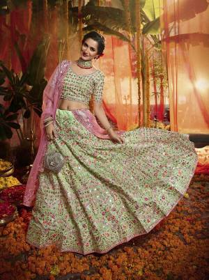 Here Is A Very Beautiful Heavy Embroidered Designer Lehenga Choli In Light Green Color Paired With Contrasting Pink Colored Dupatta. Its Lovely Blouse and Lehenga are Fabricated On Orgenza Paired With  Net Fabricated Dupatta. Its Pretty Color Pallete And Attractive Embroidery Will Earn You Lots Of Compliments From Onlookers.