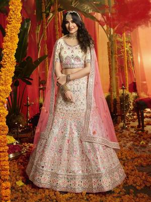 Here Is A Very Beautiful Heavy Embroidered Designer Lehenga Choli In Off-White Color Paired With Contrasting Pink Colored Dupatta. Its Lovely Blouse and Lehenga are Fabricated On Orgenza Paired With  Net Fabricated Dupatta. Its Pretty Color Pallete And Attractive Embroidery Will Earn You Lots Of Compliments From Onlookers.