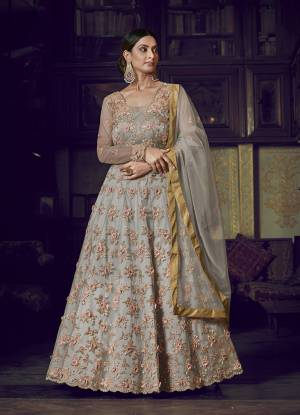 Flaunt Your Rich And Elegant Taste Wearing This Designer Semi-Stitched Floor Length Gown In Grey Color Paired With Grey Colored Dupatta. This Pretty Gown And Dupatta Are Fabricated On Net Beautified With Pretty Embroidery Giving An Attractive Look.