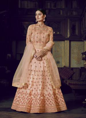 Look Pretty In This Beautiful Designer Floor Length Gown In Peach Color Paired With Peach Colored Dupatta. This Semi-Stitched Gown And Dupatta Are Fabricated On Net Beautified With Pretty Embroidery. Buy Now.