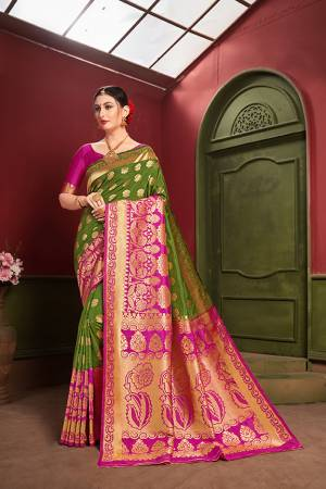 Adorn A Royal Traditional Look Wearing This Designer Silk Based saree In Green And Rani Pink color. This Saree IS Fabricated On Banarasi Art Silk Paired With Art Silk Fabricated blouse. It Is Beautified With Rich Weave All Over.