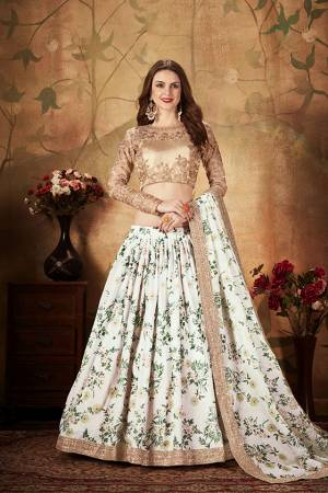 Get Ready For The Upcoming Wedding Season With This Beautiful Designer Lehenga Choli In Beige Colored Blouse Paired with Contrasting White Colored Lehenga And Dupatta. Its Pretty Embroidred Blouse Is Fabricated On Orgenza Paired with Orgenza Fabricated Printed Lehenga and Dupatta.
