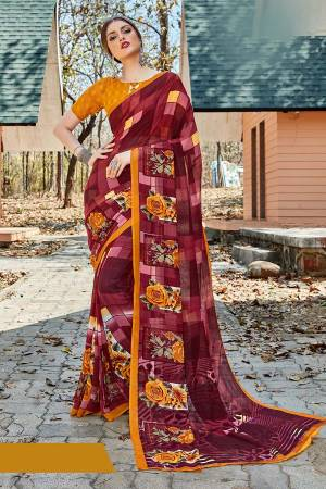 For Your Casual Or Semi-Casual Wear, Grab This Printed saree In Maroon Color paired With Musturd Yellow Colored blouse. This Saree And Blouse Are Fabricated On Georgette Beautified With Prints. It Is Light In Weight And Easy To Carry All Day Long.