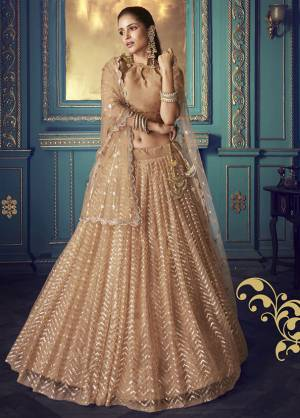Get Ready For The Upcoming Wedding and Festive Season Wearing This Heavy Designer Lehenga Choli In Light Brown Color. Its Blouse And Lehenga Are Fabricated On Net Beautified With Heavy Attractive Embroidery.