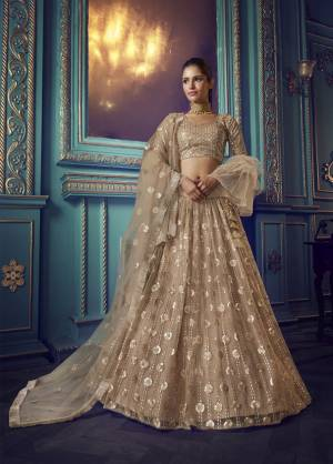 Get Ready For The Upcoming Wedding and Festive Season Wearing This Heavy Designer Lehenga Choli In Beige Color. Its Blouse And Lehenga Are Fabricated On Net Beautified With Heavy Attractive Embroidery.