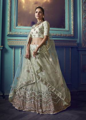 Here Is A Very Pretty Heavy Designer Lehenga Choli In Pastel Green Color. Its Pretty Heavy Embroidered Lehenga, Choli And Dupatta Are Fabricated On Net. Its Fabric, Color And Embroidery Will Earn You Lots Of Compliments From Onlookers.