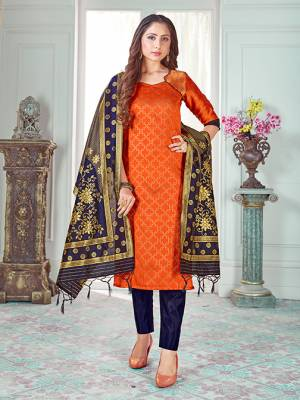 Here Is A Rich And Elegant Looking Silk Based Straight Suit In Orange Colored Top Paired With Navy Blue Colored Bottom And Dupatta. Its Top And Dupatta Are Fabricated On Banarasi Silk Paired with Art Silk Bottom.