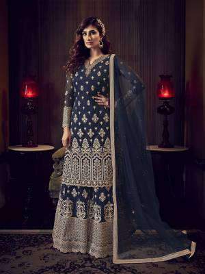 Get Ready For The Upcoming Wedding And Festive Season Wearing This Heavy Designer Sharara Suit In Navy Blue Color. This Sharara Suit In Fabricated On Net Beautified With Heavy Detailed Embroidery Giving An Attractive Look.