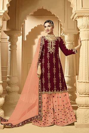 Here Is A Very Beautiful Designer Heavy Suit In Maroon Color Paired With Peach Colored bottom And Dupatta. Its Embroidered Top And Bottom Are Georgette Based Paired with Net Fabricated Dupatta.