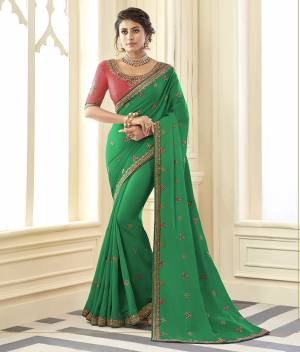 Grab This Very Pretty Designer Saree In Green Color Paired With Contrasting Pink Colored Blouse. This Saree Is Fabricated On Satin Silk Paired With Art Silk Fabricated Blouse. It Is Beautified With Detailed Embroidery Work Giving An Attractive Look.
