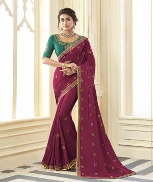 You Will Definitely Earn Lots Of Compliments Wearing This Designer Saree In Magenta Pink Color Paired With Contrasting Green Colored Blouse. This Embroidered Saree Is Satin Silk Based Paired With Art Silk Fabricated Blouse. Buy Now.