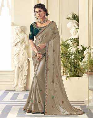 Get Ready For the Upcoming Wedding And Festive Season Wearing This Beautiful Designer Embroidered Saree In Light Grey Color Paired With Contrasting Teal Green colored Blouse. This Saree Is Fabricated On Satin Silk Paired With Art Silk Fabricated Blouse. Its Rich Fabric And Color Will Earn You Lots Of Compliments From Onlookers.