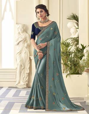 Grab This Very Pretty Designer Saree In Steel Blue Color Paired With Contrasting Navy Blue Colored Blouse. This Saree Is Fabricated On Satin Silk Paired With Art Silk Fabricated Blouse. It Is Beautified With Detailed Embroidery Work Giving An Attractive Look.