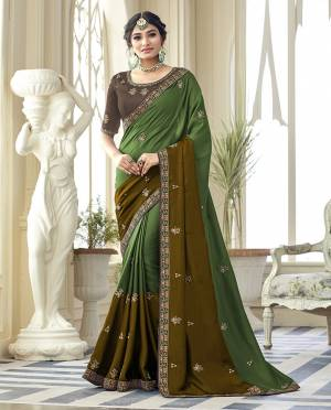 Flaunt Your Rich And Elegant Taste Wearing This Designer Saree In Green And Brown Color Paired With Brown Colored Blouse. This Saree Is Fabricated On Satin Silk Paired With Art Silk Fabricated Blouse.