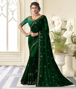 Get Ready For the Upcoming Wedding And Festive Season Wearing This Beautiful Designer Embroidered Saree In Dark Green Color Paired With Contrasting Green colored Blouse. This Saree Is Fabricated On Satin Silk Paired With Art Silk Fabricated Blouse. Its Rich Fabric And Color Will Earn You Lots Of Compliments From Onlookers.