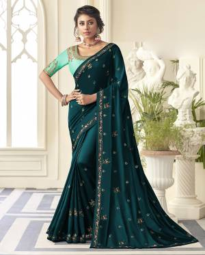 Grab This Very Pretty Designer Saree In Teal Blue Color Paired With Contrasting Turquoise Blue Colored Blouse. This Saree Is Fabricated On Satin Silk Paired With Art Silk Fabricated Blouse. It Is Beautified With Detailed Embroidery Work Giving An Attractive Look.