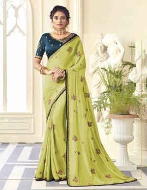 You Will Definitely Earn Lots Of Compliments Wearing This Designer Saree In Light Green Color Paired With Contrasting Teal Blue Colored Blouse. This Embroidered Saree Is Satin Silk Based Paired With Art Silk Fabricated Blouse. Buy Now.