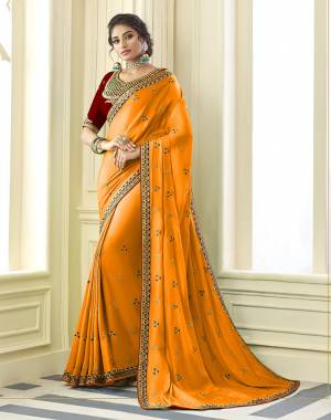 Get Ready For the Upcoming Wedding And Festive Season Wearing This Beautiful Designer Embroidered Saree In Musturd Yellow Paired With Contrasting Red colored Blouse. This Saree Is Fabricated On Satin Silk Paired With Art Silk Fabricated Blouse. Its Rich Fabric And Color Will Earn You Lots Of Compliments From Onlookers.