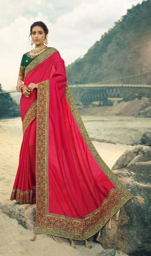 Here Is A Beautiful Designer Saree In Rani Pink Color Paired With Contrasting Dark Green Colored Blouse. This Saree Is Fabricated On Vichitra Silk With Jacquard Silk Border Paired With Art Silk Fabricated Blouse. This Pretty Saree Is Easy To Drape And Carry All Day Long. Buy Now.