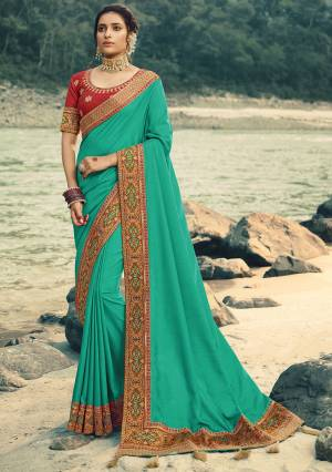Adorn The Pretty Aneglic Look Wearing This Beautiful Attractive Designer Saree In Sea Green Color Paired With Red Colored blouse. This Saree Is Fabricated On Vichitra Silk Paired With Art Silk Fabricated Blouse. It Is Beautified With Jacquard Silk Colorful Border.
