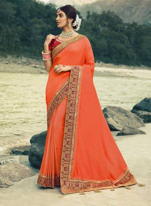 Here Is A Beautiful Designer Saree In Orange Color Paired With Contrasting Red Colored Blouse. This Saree Is Fabricated On Vichitra Silk With Jacquard Silk Border Paired With Art Silk Fabricated Blouse. This Pretty Saree Is Easy To Drape And Carry All Day Long. Buy Now.