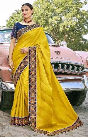 Celebrate This Festive Season In This Very Pretty Yellow Colored Designer Saree Paired With Contrasting Navy Blue Colored Blouse. This Saree and Blouse Are Silk Based Beautified With Detailed Embroidery.