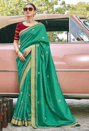 Grab This Pretty Elegant Looking Designer Saree In Green Color Paired With Contrasting Red Colored Blouse. This Saree And Blouse Are Silk Based Beautified With Embroidery. Buy Now.