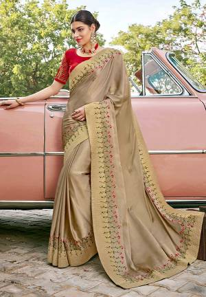 Adorn The Pretty Angelic Look Wearing This Heavy Designer Saree In BeigeColor Paired With Contrasting Red Colored Blouse. This Saree Is Fabricated On Satin Silk Paired With Art Silk Fabricated Blouse. Its Pretty Color Pallete Will Give An Attractive Look To Your Personality.