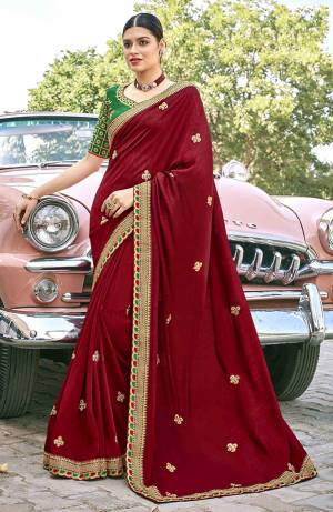 Celebrate This Festive Season In This Very Pretty Maroon Colored Designer Saree Paired With Contrasting Green Colored Blouse. This Saree and Blouse Are Silk Based Beautified With Detailed Embroidery.