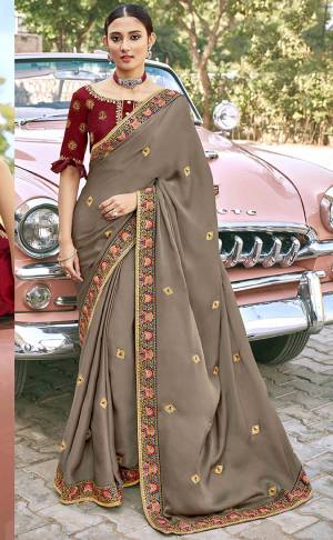 Look Attractive Wearing This Grey Colored Saree Paired With Maroon Colored Blouse.  This Heavy Designer Saree Is Silk Based Which Gives A Rich Look To Your Personality. Buy This Pretty Saree Now.